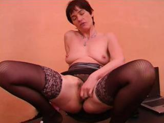 older dame with short hair in dark nylons gives a